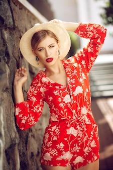 빨간 양복과 모자에 젊은 유행 아름다운 섹시한 여자는 벽돌 벽 근처에 서