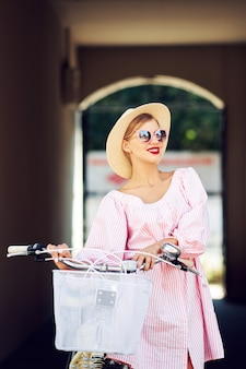 Young fashionable beautiful sexy girl in a pink suit and a straw hat ride around the city on a bicycle and laughs. the concept of a healthy lifestyle and stylish lifestyle