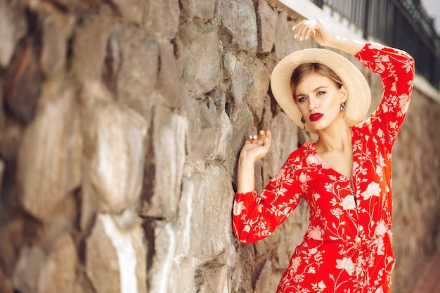 Young fashionable beautiful sexy girl in a red suit and hat stands near a brick wall Premium Photo