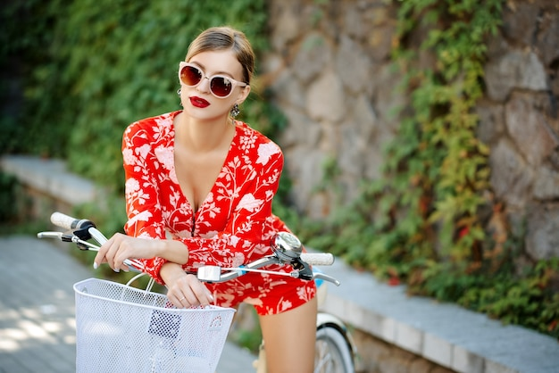 Young fashionable beautiful sexy girl in a red suit in summer in a city wearing sunglasses riding a bicycle