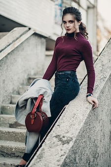 Young fashionable beautiful woman in a black jeans and with a dark red bag. professional model