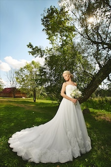 Young fashionable bride, beautiful blonde model girl with stylish wedding hairstyle, in white lace dress with bouquet of flowers in her hands posing outdoors at the sunset