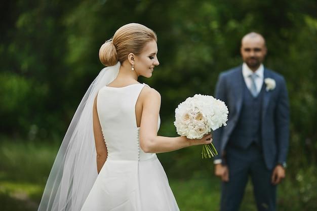 彼女の手に花の花束を持つスタイリッシュな白いドレスの若いおしゃれな花嫁は屋外に立って、新郎を待っています