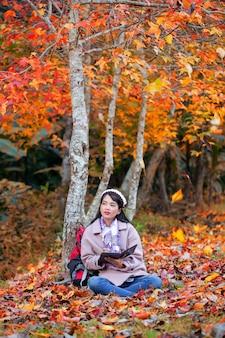 秋の公園に座っているデジタルタブレットでファッショナブルな少女