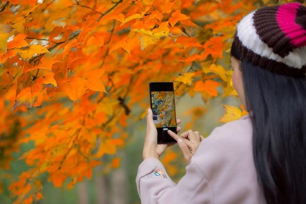 写真を撮る携帯電話を持つファッショナブルな少女