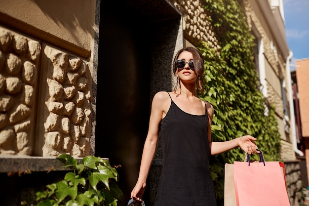 Young fashionable good-looking brunette caucasian woman in sunglasses and black dress leaving store with shopping bags in hands and relaxed face expression. lifestyle concept