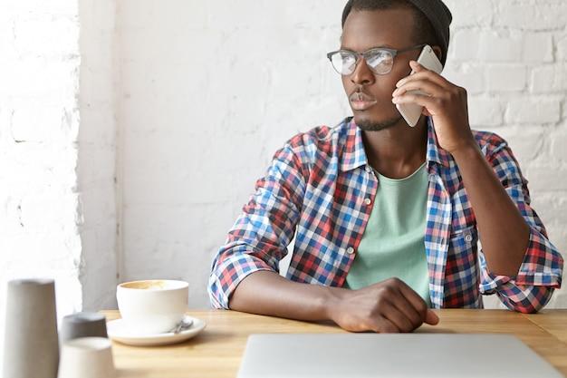 Молодой модный парень сидит в кафе со смартфоном