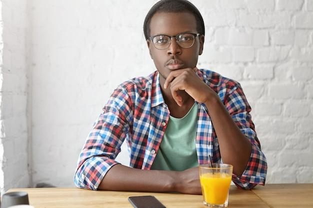カフェに座っている若いおしゃれな男