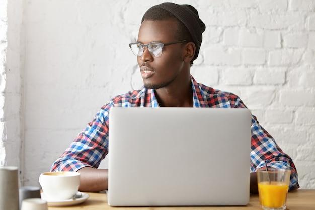 Giovane ragazzo alla moda seduto in un bar con il computer portatile
