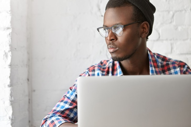 Young fashionable guy sitting at a cafe with laptop