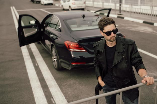 車の近くの眼鏡をかけた若いファッショナブルな男。