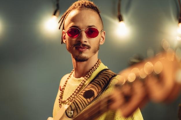 Молодой модный мужчина в розовых очках с радостью играет на гитаре