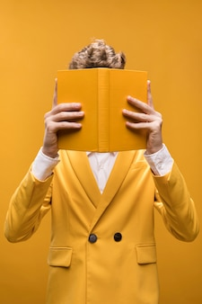 Young fashionable man reading a book