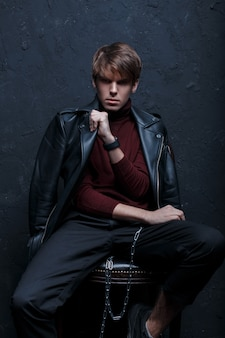 Young fashionable man in a retro style jacket in red golf in stylish jeans in black sneakers with a silver metal chain sits and poses on a chair in a dark studio. serious stylish guy