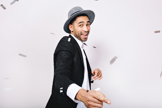 Young fashionable man in suit, hat having fun, dancing in tinsels isolated,. celebration, party time, expressing posititvity, enjoying, leisure, happiness.
