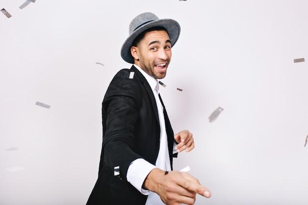 Giovane uomo alla moda in vestito, cappello divertendosi, ballando in orpelli isolati. celebrazione, tempo di festa, espressione di positività, divertimento, svago, felicità.