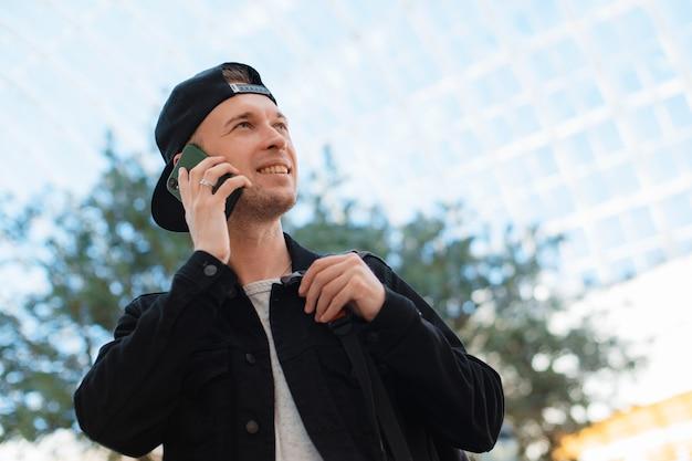 검은 모자를 쓰고 선글라스를 끼고 스마트폰을 든 젊은 세련된 현대 남성이 태양의 일몰 광선 아래 터널에 있는 도시 배경에서 전화로 이야기합니다.