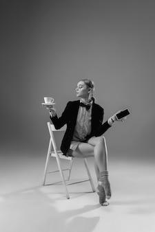 Молодая модная стильная женщина в куртке и носках работает из домашней моды во время изоляции
