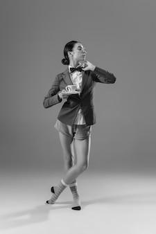 自宅で仕事をしているジャケットと靴下を身に着けている若いファッショナブルでスタイリッシュな女性。