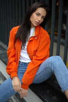 Молодая модная девушка-подросток гуляет по городу летом в модной куртке и джинсах