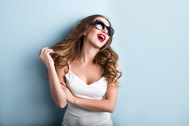 Young fashionable woman on blue background. emotions.