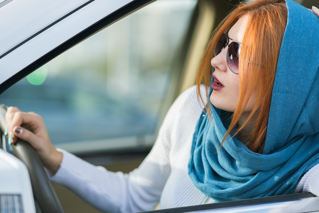 Молодой модный женщина водитель в шарф и солнцезащитные очки, за рулем автомобиля.