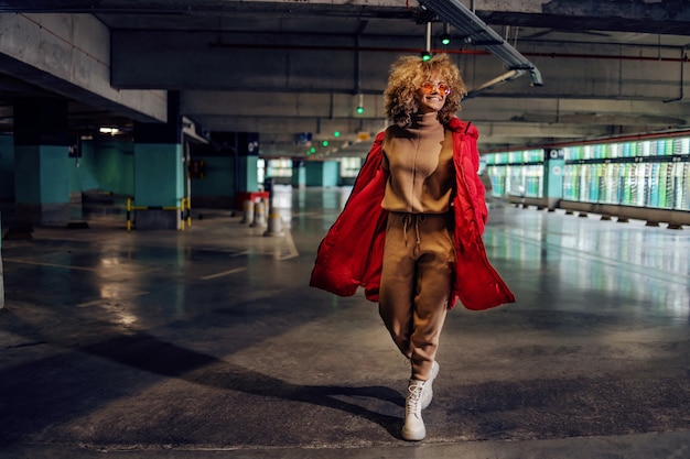 ジャケットのポケットに手を握り、地下駐車場を歩いているファッショナブルな若い女性。