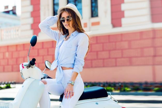 Молодая модная женщина в повседневном наряде сидит на скутере на улице