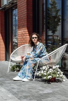 안경을 쓴 세련된 젊은 여성이 새로운 여름 옷 컬렉션에서 포즈를 취하는 의자에 앉아 있다