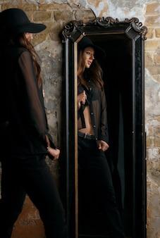 ヴィンテージミラーに立っているスタイリッシュな黒の衣装を着て若いファッショナブルな女性