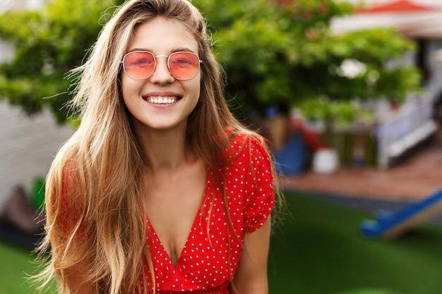 웃고 웃고, 화창한 날에 녹색 공원에 서있는 금발 머리를 가진 젊은 유행 여자