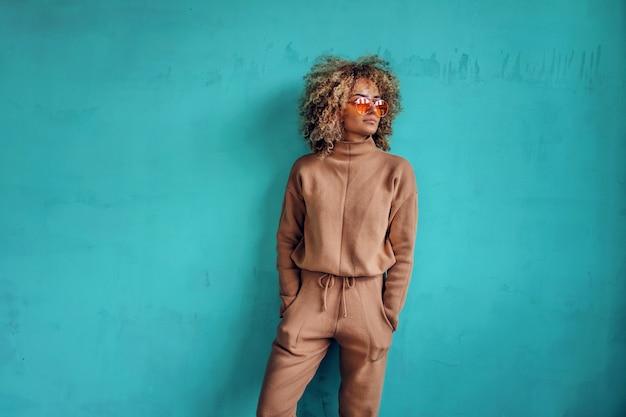 ポケットに手をつないで壁の前に立っている巻き毛の若いファッショナブルな女性。