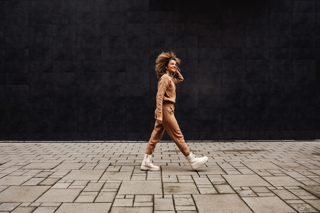 通りを歩いて音楽を聴いている巻き毛の若いファッショナブルな女性。