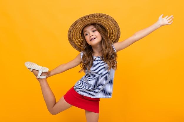 Молодая модница флиртует в соломенной шляпе на желтом фоне с копией пространства.