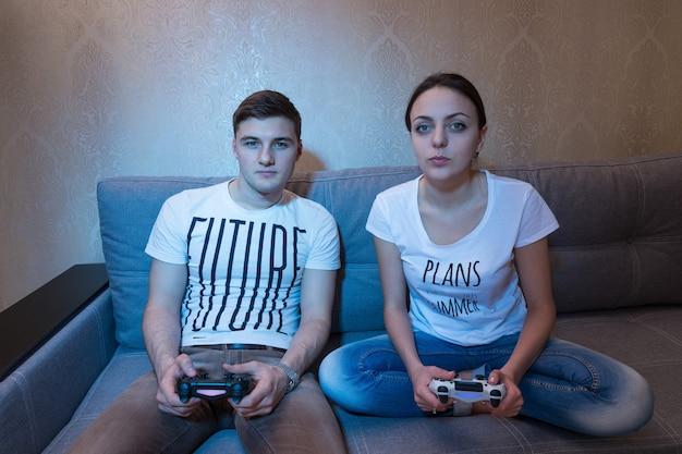 집에서 함께 소파에 앉아 치열한 경쟁적인 표정으로 비디오 게임을 하는 젊은 패셔너블한 커플