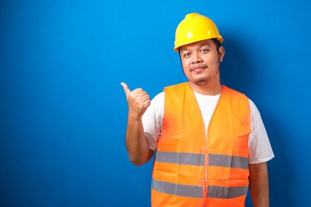 파란색 배경 위에 있는 젊은 뚱뚱한 아시아 남자는 계약자 유니폼과 안전 헬멧을 쓰고 행복한 얼굴로 옆구리를 엄지손가락으로 가리키고 보여줍니다.