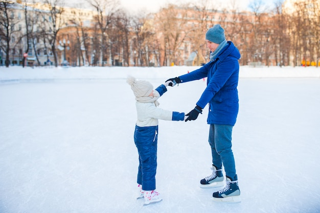 Young father and adorable little girl have fun on skating rink outdoors