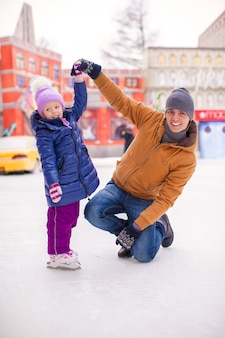 Young father and adorable little girl have fun on skating rink