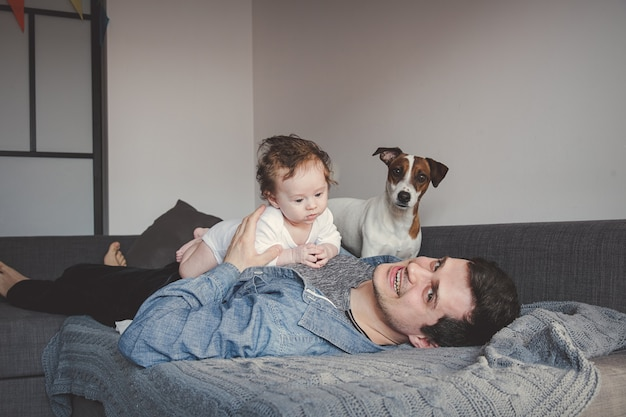 Молодой отец и мальчик в домашнем интерьере с собакой