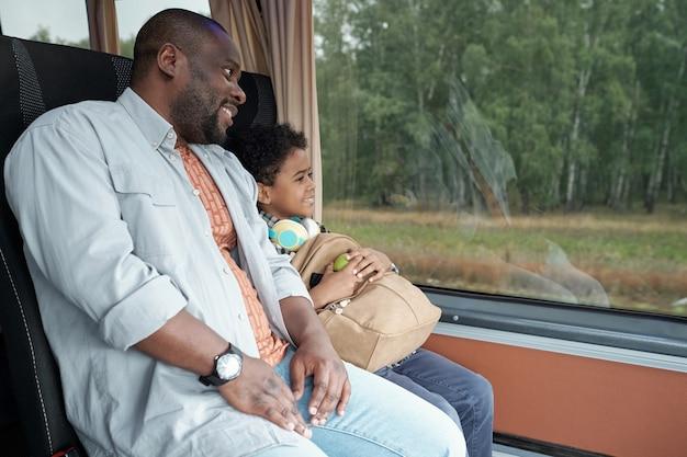 Молодой отец и милый сын с рюкзаком, глядя через окно автобуса