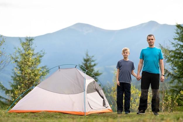 젊은 아버지와 그의 자식 아들이 함께 여름 산에서 하이킹을 하고 있습니다. 캠핑 여행에 활동적인 가족입니다.