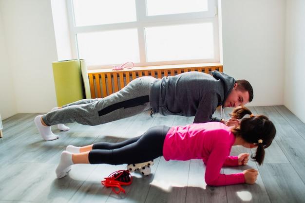 젊은 아버지와 그의 귀여운 작은 딸은 집에서 바닥에 판자를하고 있습니다. 가족 피트니스 운동. 귀여운 꼬마와 아빠가 실내 매트 훈련을하고 있으며, 방에있는 창문 근처에서 운동을합니다.