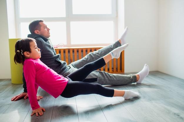Молодой отец и его милая маленькая дочь делают обратную планку с подъемом ног на полу дома. семейная фитнес-тренировка. милый ребенок и папа тренируются на коврике в помещении у окна в комнате.
