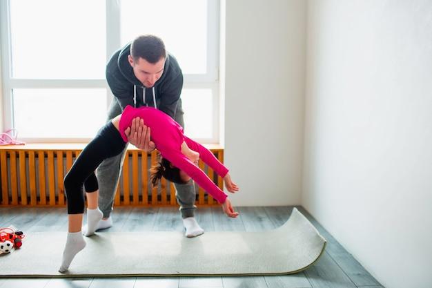 젊은 아버지와 그의 귀여운 작은 딸이 다리 포즈에서 집에서 운동을했습니다. 귀여운 아이와 아빠가 실내 매트에서 훈련하고 있습니다. 그들은 운동복을 입고 방의 창 근처에서 운동을합니다.
