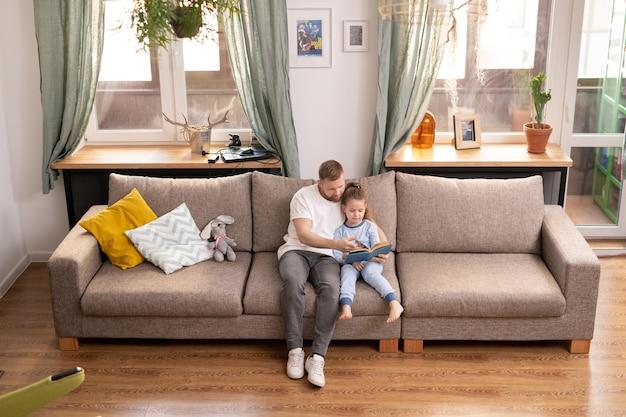 若い父と彼のかわいい娘はソファに座って、検疫のために家にいる間、物語やおとぎ話の本を読んでいます