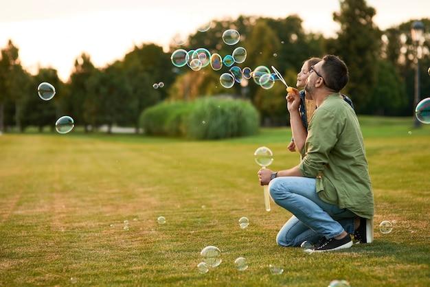 Молодой отец и его маленькая девочка веселятся, дуя мыльные пузыри в летний день, дочь и