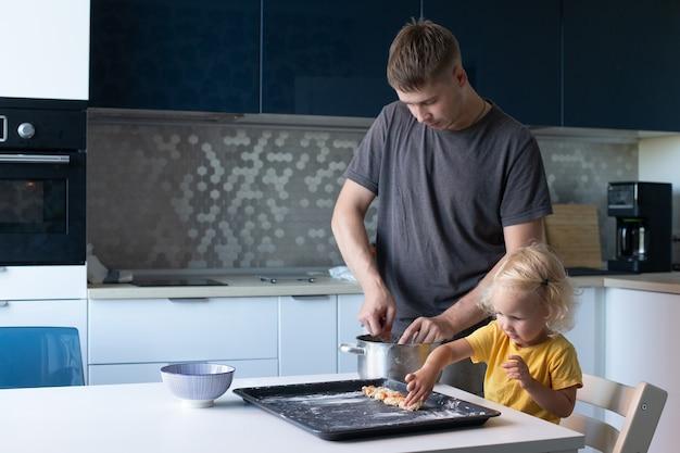 若い父と彼の小さなかわいい娘が一緒に料理をしています。家族はキッチンで楽しくクッキーを作っています。女の子は金髪で巻き毛です