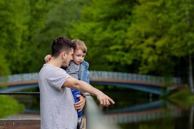 Молодой отец и его улыбающийся сын в парке, обнимаются и наслаждаются временем вместе, празднование дня отца.