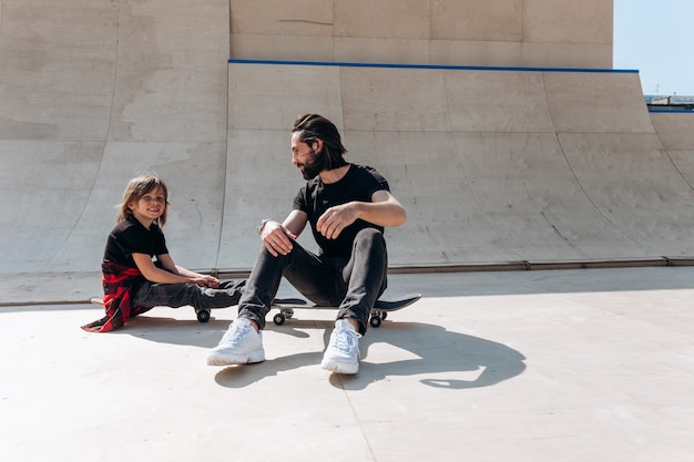 캐주얼한 옷을 입은 젊은 아버지와 그의 아들이 화창한 날 스케이트 공원에서 스케이트보드에 앉아 있습니다.