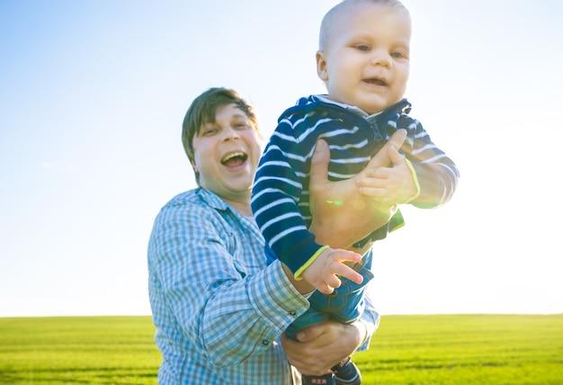 Молодой отец и его сын веселятся, играя на зеленом поле